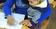 Kucağında çocuklarıyla okuma yazma öğreniyorlar
